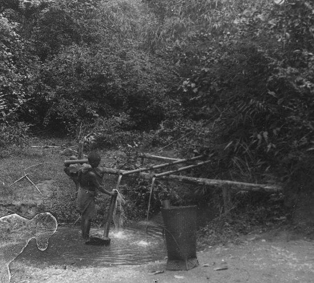 Femme remplissant d'eau un tube en bambou