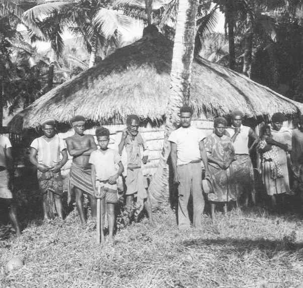 Groupe de Canaques devant une case circulaire
