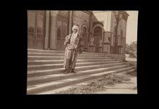 Personnage debout sur des marches d'un bâtiment monumental
