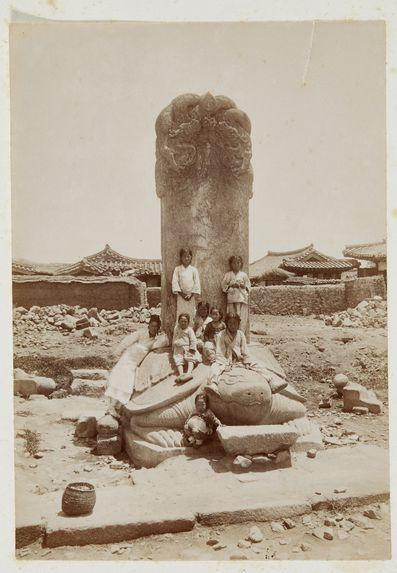Sans titre [Groupe d'enfants posant sur une stèle]