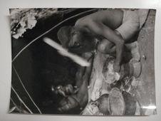Femme Babenzelé pile du maïs ou du manioc échangé aux noirs