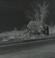 Sans titre [femme devant une habitation, au bord d'une route]