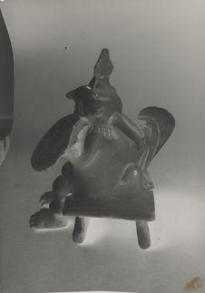 Personnage assis en céramique sur un siège, avec casque et bouclier