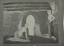 Village du chef. Femmes écrasant le mil sur le seuil de leur case