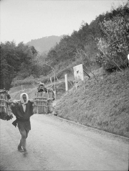 Sans titre [homme portant des fagots de bois et bâtiment dans un espace boisé]
