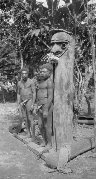 Deux hommes Small Nambas devant tambour à fente dressé