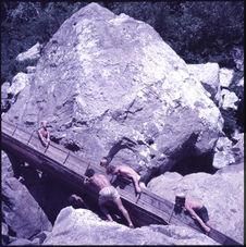 Sans titre [hommes portant une pirogue sur des rochers]