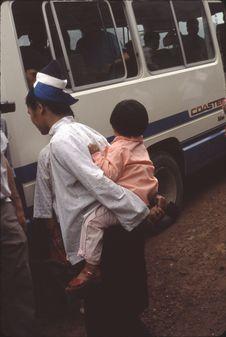 Neitian [femme portant un enfant sur son dos avec les bras, près d'un minibus]