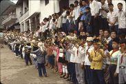 Début réception Bibei [enfants alignés en costume dans la rue tenant des fleurs...