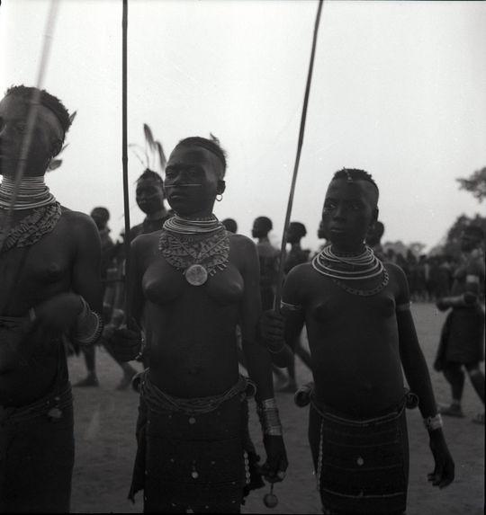 Initiés au cimier de plumes [portrait de trois jeunes femmes tenant de longs et fins bâtons]