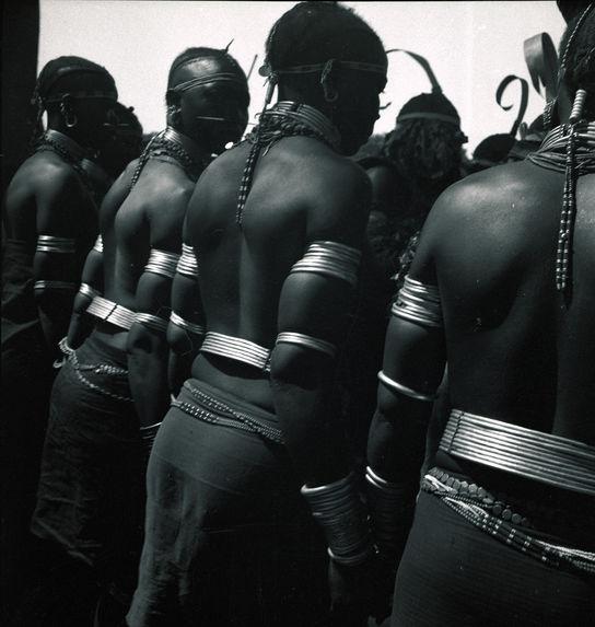 Femmes nues avec leurs bijoux rituels [groupe en tenue de cérémonie et portant des coiffes hautes et recourbées]