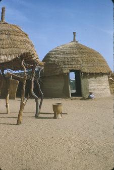Sans titre [un récipient en bois (baratte ?) devant deux huttes]
