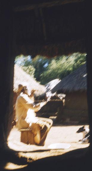 Sans titre [vieil homme assis sur un banc à proximité d'habitations]