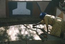 Sans titre [femme venda réalisant des motifs en terre sur le sol d'une...