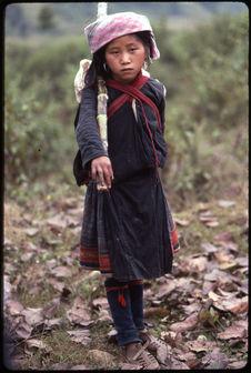 Petite fille portant un paquet avec un bambou sur l'épaule