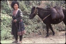 Femme revenant des champs avec son cheval de bât
