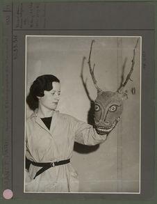 Denise Paulme tenant un masque tibétain pour danse rituelle