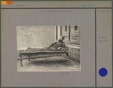 Sarte étendu sur un lit de bois colorié
