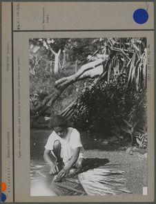 Femme nattant ensemble deux feuilles de cocotier