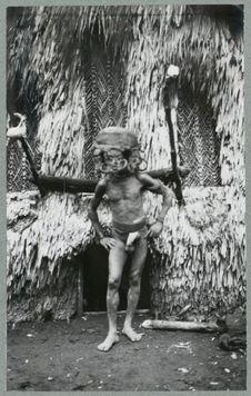 Homme masqué devant maison cérémonielle