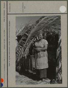 Femme en costume traditionnel, portant le tablier-ceinture ta'ouala