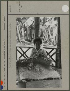 Femme tressant une natte dans une maison traditionnelle ouverte