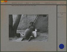 Femme assyrienne barattant dans la cour d'une ferme