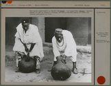 Deux hommes montrent comment on joue du tambour à friction