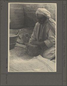 Le gardien du grenier collectif mesure du grain dans l'akarwi
