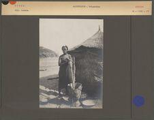 Femme béribéri pilant le mil devant sa hutte