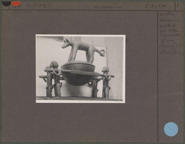 Quatre hommes portant un vase surmonté d'un chien ou d'un loup