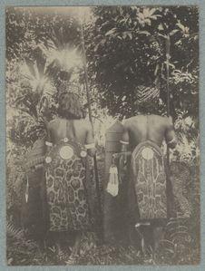 Twee Batang Loepor Dayaks in vol ornaat van achteren gezien