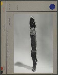 Statuette en bois, oeil figuré par un bouton en fer
