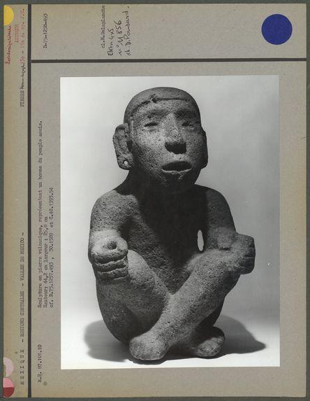 Sculpture en pierre volcanique grise, un homme du peuple