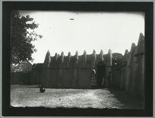 Soudan. Bouna [trois femmes debout  à la porte d'une habitation en adobe]
