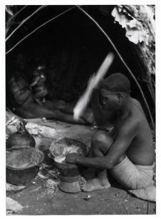 Femme pygmée pilant du maïs échangé aux Noirs
