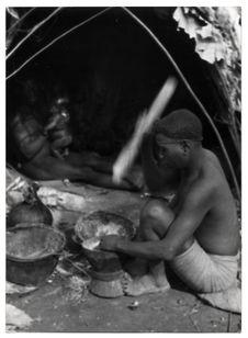 Cette femme pygmée pile du maïs échangé au noir