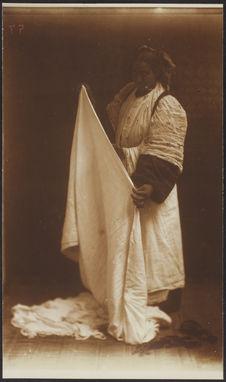 Sans titre [femme préparant un voile pour l'habillement]