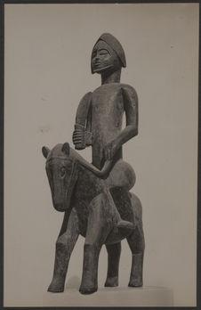 Sculpture sur bois d'un génie à cheval, armé d'un sabre