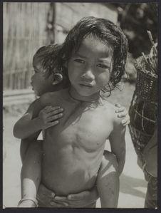 Photo[graphie] de Moys [portrait d'un petit garçon nu portant un bébé sur son...