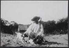 Sans titre [portrait d'un homme accroupi, armé d'un fusil et caressant deux...