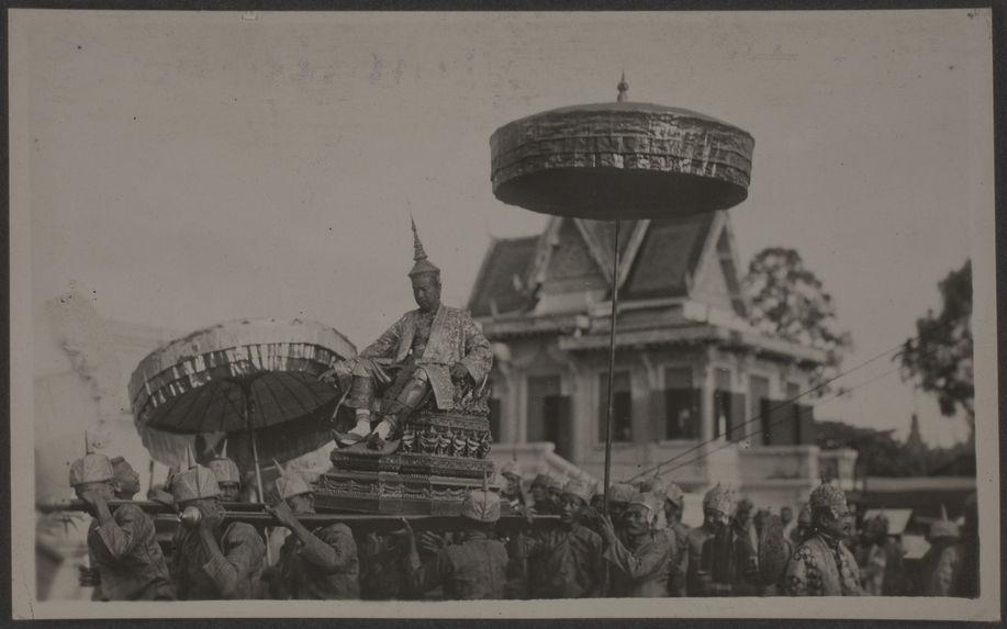S.M. Monivong quitte le Palais Royal en chaise à porteurs pour défiler dans Phnom Penh pavoisée