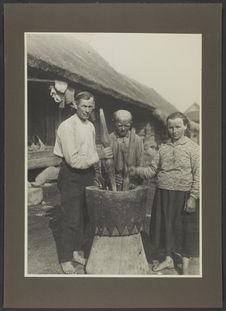 [Titre en lituanien]. [Deux hommes et une femme tenant deux pilons autour d'un...