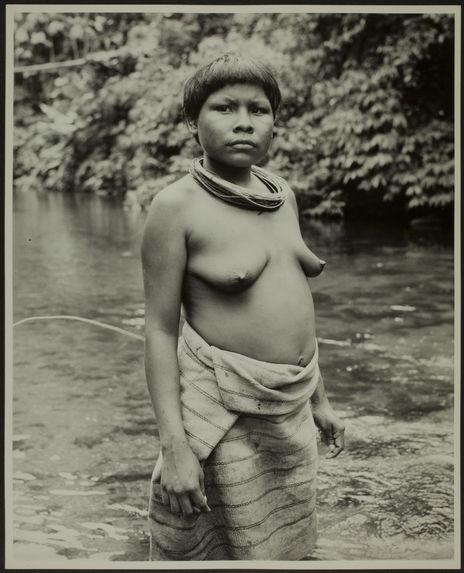 Sans titre [femme de trois quarts, torse nu, avec des colliers et une jupe au bord d'une rivière]