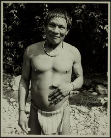Sans titre [homme debout, en pagne, avec un collier et des bracelets au bord...