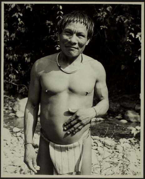 Sans titre [homme debout, en pagne, avec un collier et des bracelets au bord d'une rivière]