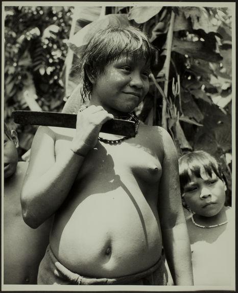Sans titre [jeune femme en buste, tenant un outil [?] en métal dans la main. En arrière-plan, deux jeunes garçons]