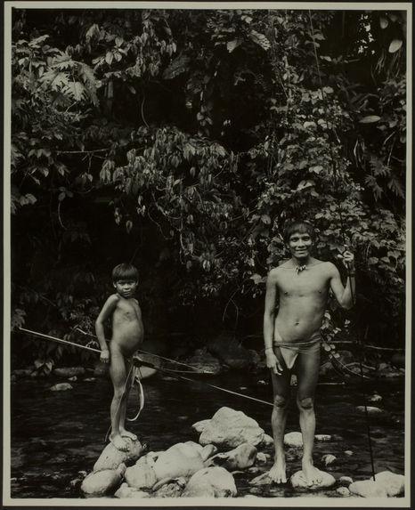 Sans titre [un jeune homme et un petit garçon de face, en pied, tiennent deux longues tiges en bois pour la pêche ? Le petit garçon tient également un arc. Ils sont debout sur des pierres de la rivière]