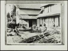 Sans titre [fabrication du papier japonais; devant un bâtiment des fagots et des...