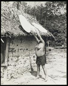Sans titre [femme installant des galettes de casabe sur le toit d'une maison...